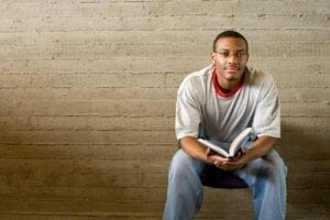 Young man sitting on bench with book