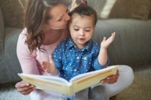Mother reading book to young child
